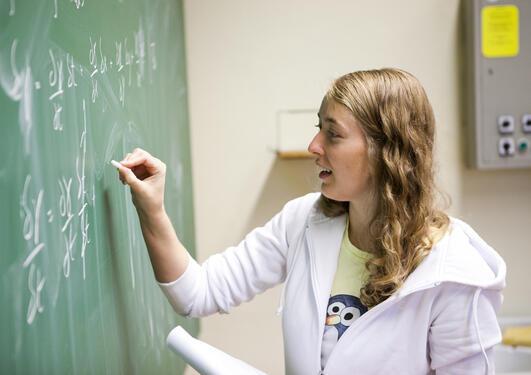 Student skriver på tavle. Matematikk.