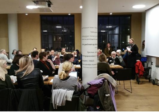 flere mennesker sitter i en cafe og hører på en taler