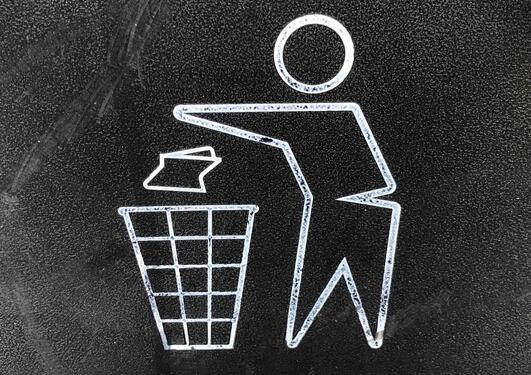 Person som kaster noe i en søppelkurv