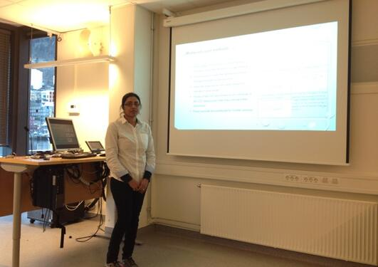 A lady standing beside a whiteboard with powerpoint presentation