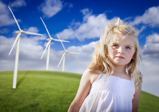 Bilde av en jente som leker nær vindmøller