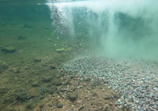 An underwater shot of gravel being added to a river bed