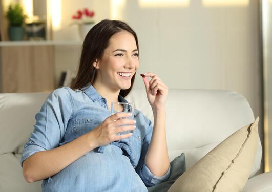 gravid sitter i sofa med glass vann og skal ta medisin