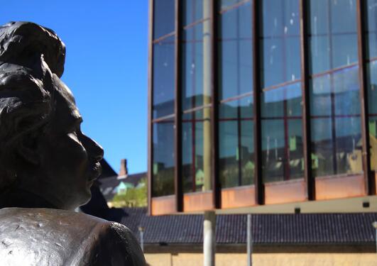edvard grieg-statue med grieghallen og griegakademiet i bakgrunnen