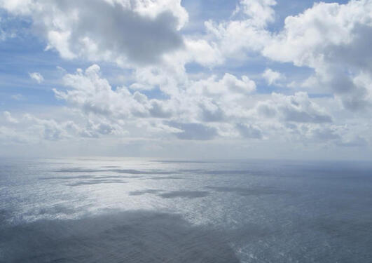 Image of the ocean with scattered clouds above. Used to illustrate article about UiB doing well in earth and marine sciences in QS by Subject rankings.