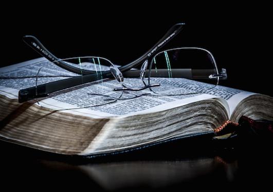 Bilde av oppslått bok med briller