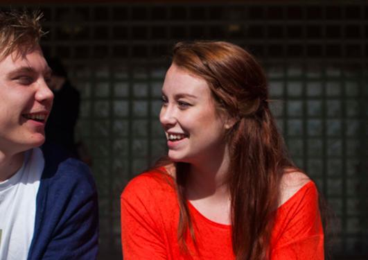 En gutt og en jente ser på hverandre og smiler