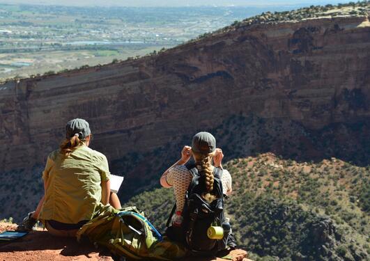 Bildet viser to studenter på ekskursjon i USA. Studentene sitter med ryggen til fotografen og skuer ut over landskapet.