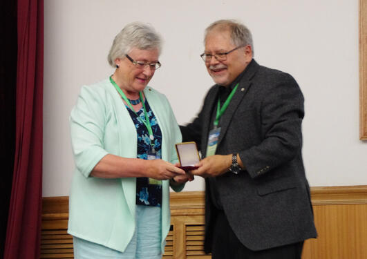 Hilary Birks receiving her Lifetime Achievement medal from John Smol at the International Paleolimnology Symposium
