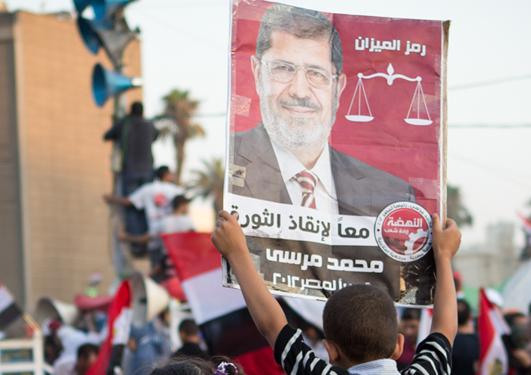 Ein gut held opp ein plakat av Muhammad Morsi, Egypts tidlegare president.
