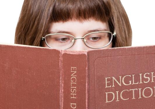Jente med briller leser i en English dictionary