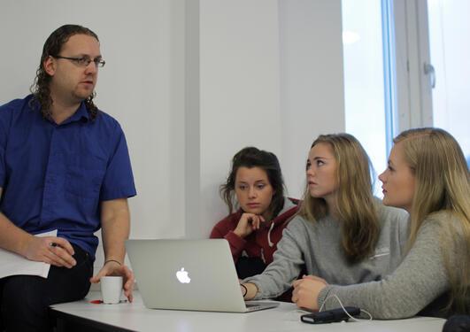 Isak Lekve, stipendiat ved Sosiologisk Institutt ved Universitetet i Bergen bistår Linn Sæthre, Maria Høyvik og Tonje Madsen med deres bidrag til Holbergprisen i skolen.