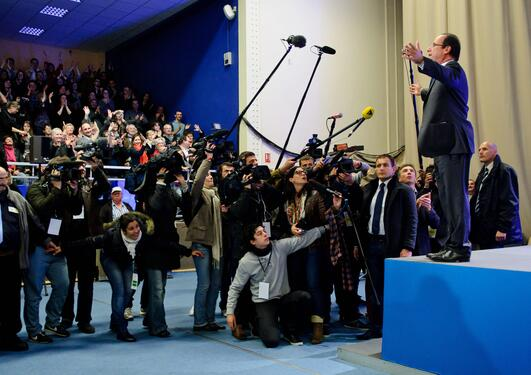 A picture of the President of France, Francois Hollande, in election campaign mode in front of a tightly packed press corps.