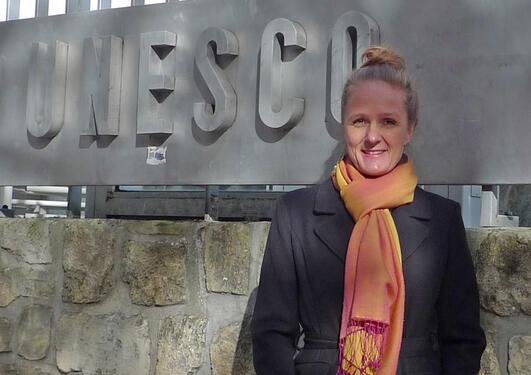 Portrait of Inger Måren standing besides the UNESCO nameplate