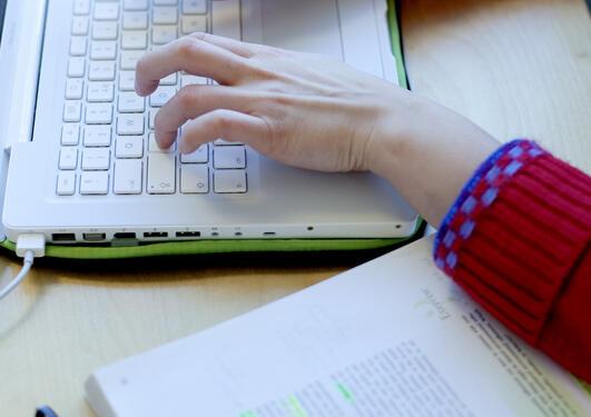 hender som taster på et lap top tastatur