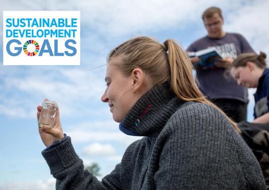Biologistudent fra Universitetet i Bergen med logo for FNs bærekraftsmål på bildet.