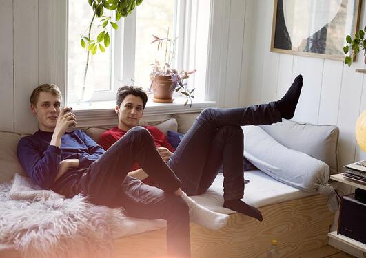 To unge gutter sitter i sofa. Foto