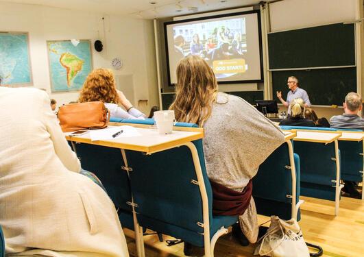 """Eivind Olsvik fra Karrieresenteret gestikulerer foran i Stort auditorium med teksten """"God start"""" på Powerpoint."""