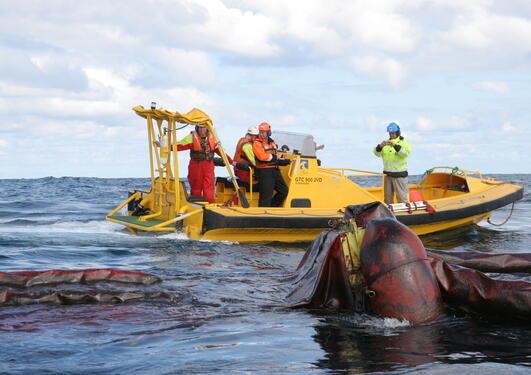 Øvelse i oljerydding i Nordsjøen. En liten båt, med fire personer, samt utstyr på havet.