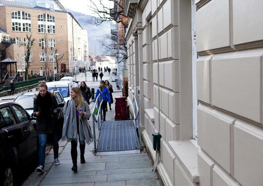 Studenter i vinterklær går i gaten utenfor Sosiologisk institutt, med SV-bygget og Ulriken i bakgrunnen.