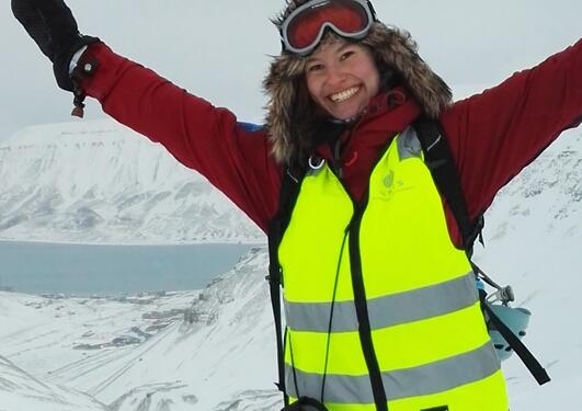 A lady in winter gear against arctic landscape