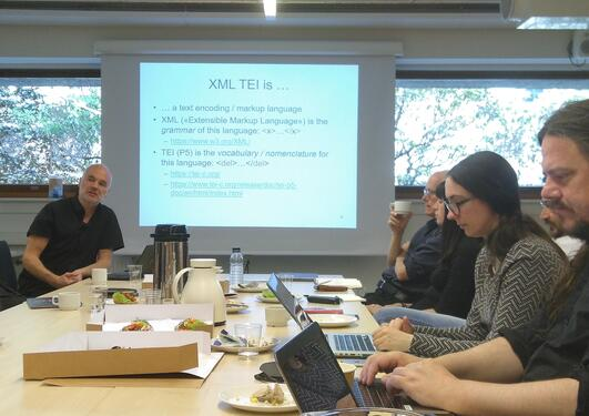 People around a table with laptops, including Alois Pichler explaining what XML is, powerpoint in the center with XML definition.