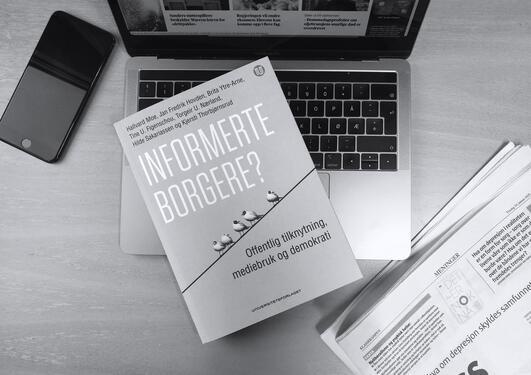 Bilde av boken med datamaskin, mobil og avis rundt.