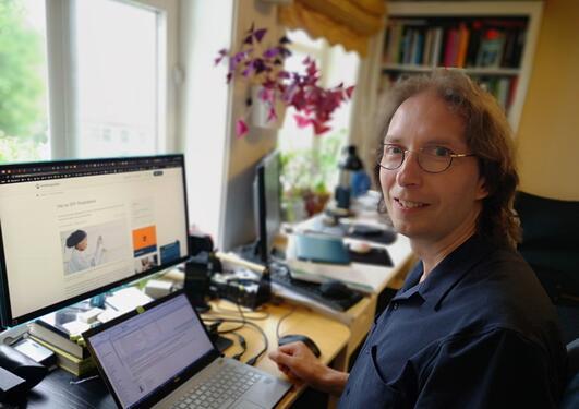 Smilande mann med briler og svart skjorte sit framfor ein laptop og ein ekstern skjerm