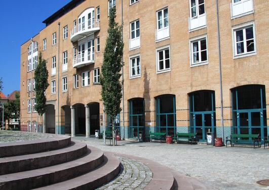 Fakultetsbygget og plassen foran i solskinn