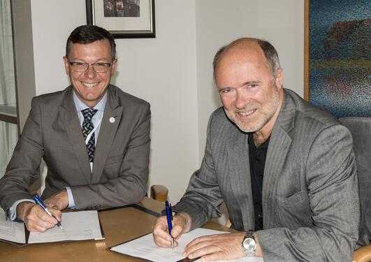 Rektor Dag Rune Olsen og BKKs konsernsjef Atle Neteland signerer avtale.