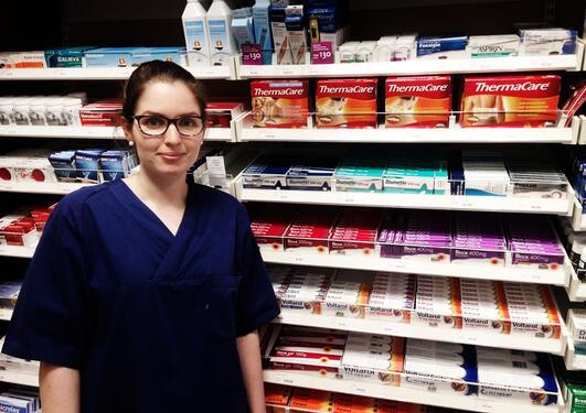 Kvinne står foran medisinhyller