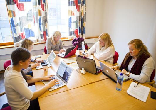 Fem kvinnelige studenter rundt et bord