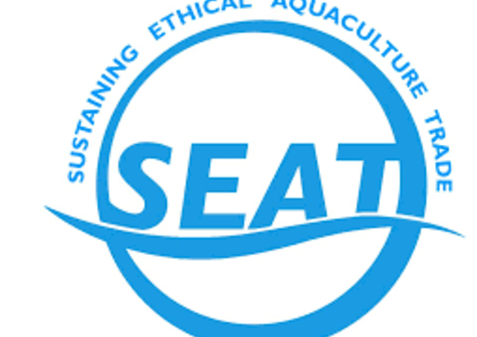 SEAT logo in blue: The abbreviation SEAT over a squiggle, surrounded by a circle. The following words written over the top of the circle: Sustaining Ethcial Aquaculture Trade