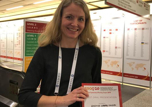 Ingvild Løberg Tangen posing with her diploma.