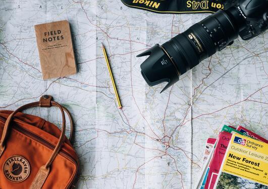 Bilde av kart, kamera, sekk og feltnotater