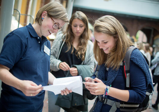 To studenter får hjelp av en UiB-ansatt