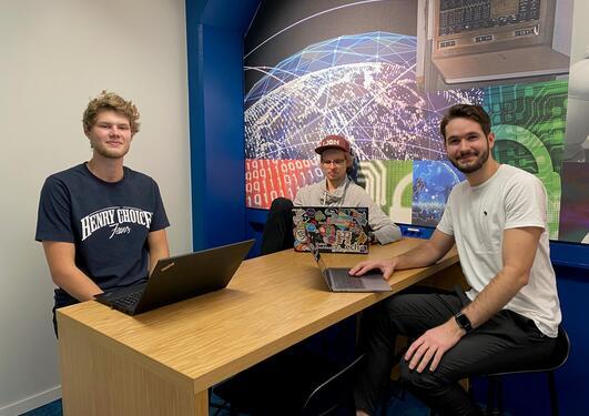 Tre menn med hver sin PC rundt et bord