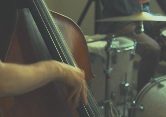 illustrasjonsfoto med utsnitt av kontrabass i forgrunn og utsnitt av jazz slagverk i bakgrunnen