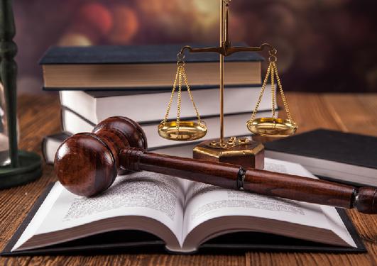 Bilde av dommerklubbe på lovbok og med skålvekten som ledsager.