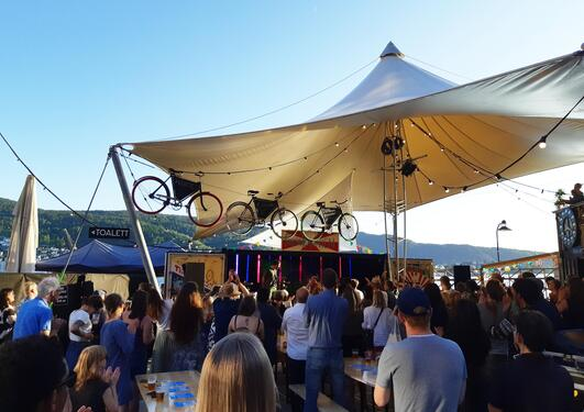 image of a crowd in front of a stage with bicycles on the roof.