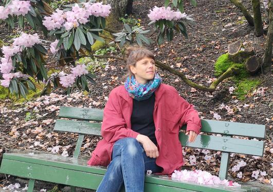 Kvinne i raud jakke, svart genser, dongeribukse og fargerikt sjal sitter på en grønn benk med rosa rhododenron-busker i bakgrunnen