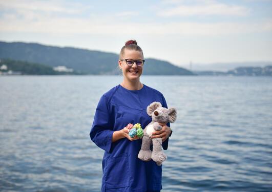 Karina Prestegård står foran havet med en kosedyr som forestiller en mus og en modell av et molekyl i hendene