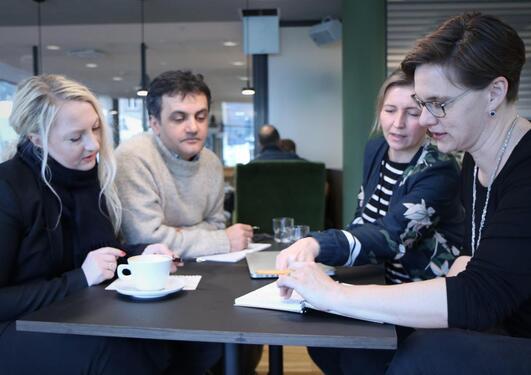 Fire personer med kaffekopper sitter ved et bord og diskuterer.