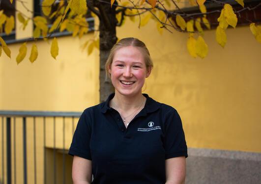 Ingeborg står foran en gul bygning og smiler til kamera
