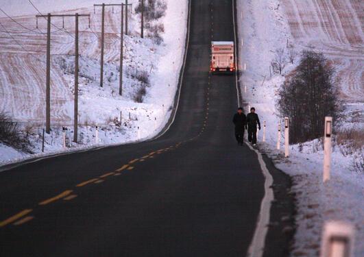 Aviste asylsøkere går langs en landevei på vinterstid