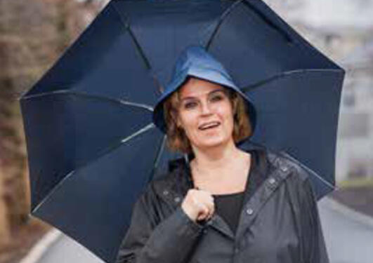 Photo of Line Bjørge in the rain with an umbrella.