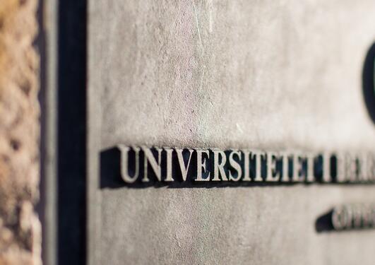 Bilde av en plakett på en murvegg med logoen og navnet til Universitetet i Bergen hvor halve bildet er ute av fokus