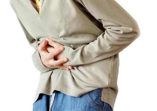Mann som holder seg til magen i smerte