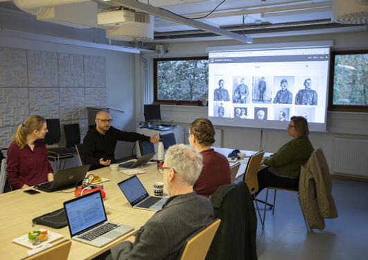 Photo of Tarje talking to a group of participants with laptops sitting around the table. The powerpoint in the background shows a series of portraits in a database