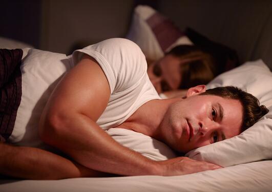 mann som som ikke får sove. Ligger i sengen ved siden av sin kone.
